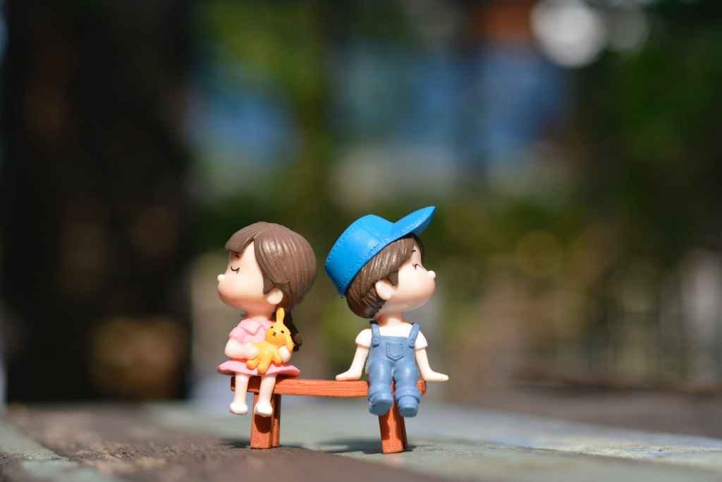 toys fighting.  Girl and boy on a bench looking away from each other.
